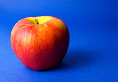 Red apple on blue background Royalty Free Stock Photos