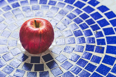 Red apple on blue. A red apple on blue mozaic table Royalty Free Stock Images