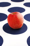 Red apple on blue and white table cloth. Red apple on blue and white polka dot table cloth Royalty Free Stock Photos