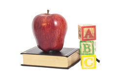 Red apple on book and ABC wooden letter blocks Royalty Free Stock Photos