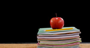 Red apple on book stack. Against black background stock video