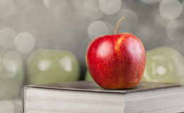 Red apple and book on a table. Royalty Free Stock Photos