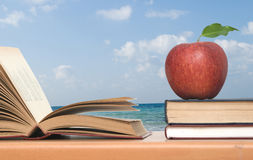 Red apple and books. On desk stock photo