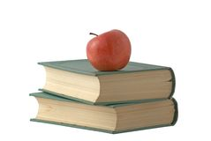 Red apple on the books. With green cover isolated over white Royalty Free Stock Image