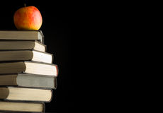 A red apple on a books. Isolated over black background Royalty Free Stock Images