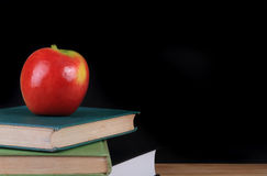 Red apple on books for back to school. A red apple on top of three old hardcover books with a blackboard background and copy space Royalty Free Stock Photo