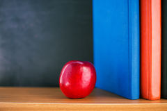 Red apple and books. Red apple lying near books and blackboard royalty free stock photos