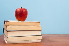 Red apple and books on a wooden table and blue background and free space for text Royalty Free Stock Photo