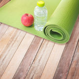 Red apple, bottle of water and yoga mat Royalty Free Stock Photo