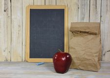 Red apple with brown paper sack Stock Photos