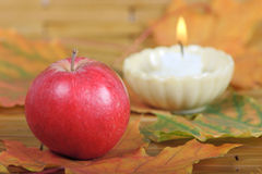 Red apple from candles on a background. Red apple on autumn leaves with burning candle on a background Royalty Free Stock Photography