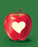 Red apple with carved heart-shaped peel. Ripe red apple with carved heart-shaped peel Royalty Free Stock Photography