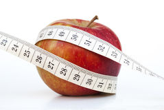 Red apple and centimeter. Apple and centimeter represents a diet and weight loss Royalty Free Stock Images