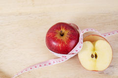 Red apple with centimeter on wood table for diet concept Stock Photo
