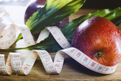 Red apple and centimeter on  a wooden table. Stock Photography