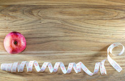 Red apple and centimeter on a wooden table. Stock Image