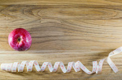 Red apple and centimeter on a wooden table. Stock Photo