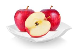 Red apple in ceramic plate beautiful shape on white background stock photography