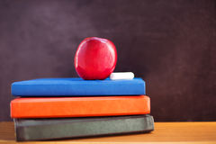 Red apple and chalk on books. Red apple and chalk lying on books near blackboard Stock Photo