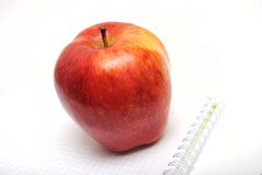 Red apple on checked copybook Royalty Free Stock Photo