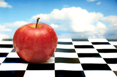 Red apple on chessboard. Red apple on a chessboard with sky in background Stock Image