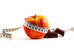 Red apple, chocolate and measuring tape. Ripe red apple, chocolate, measuring tape  on a white background Stock Image