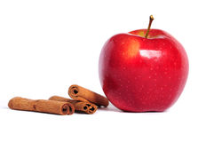 Red apple and cinnamon. Red apple and three cinnamon sticks on white royalty free stock images