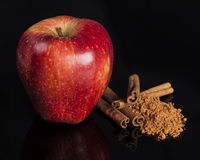 Red apple and cinnamon. On reflection surface Royalty Free Stock Photo
