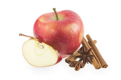 Red apple with cinnamon and star anise. On a white background Stock Photos