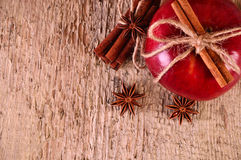 Red apple with cinnamon sticks and anise. On wooden background Stock Photos