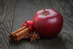 Red apple with cinnamon sticks and anise. On wooden table Royalty Free Stock Image