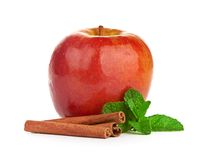Red apple, cinnamon sticks and mint leaves Royalty Free Stock Images