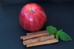 Red Apple, cinnamon sticks and mint leaves. On a black background Stock Images
