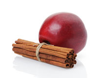 Red apple with cinnamon sticks on white. Red apple with cinnamon sticks, isolated on white background Stock Photos