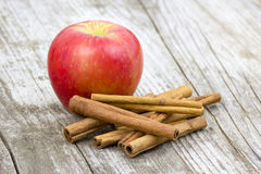 Red apple and cinnamon sticks. Wooden background Royalty Free Stock Images