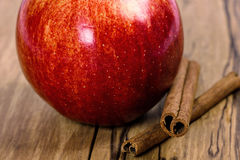 Red apple with cinnamon sticks. On wooden table Stock Photo