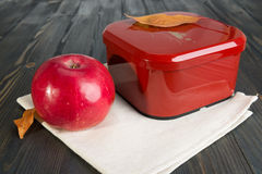 Red apple and a closed box for school lunch. Red apple and a closed box for school breakfast on the dark wooden surface Royalty Free Stock Photography