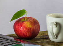 Red apple and coffee cup near notebook on plank Royalty Free Stock Photos