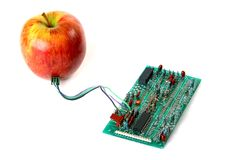 Red apple connected to the electric board Royalty Free Stock Photography