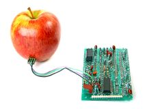 Red apple connected to the electric board Stock Photos