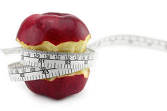 Red apple core and measuring tape Royalty Free Stock Photos