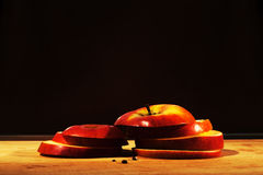Red apple cut in pieces on wooden board. Apple on black background Royalty Free Stock Image