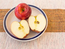 Red apple cut into white bowl on a cotton towel. Red and fresh apple cut into a white bowl on a cotton towel for delicious, tasty and healthy food Royalty Free Stock Images