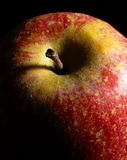 Red apple detail. Detail of a red apple in dark back Royalty Free Stock Image