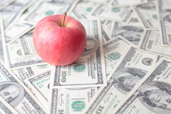 Red apple on dollar bills Stock Image