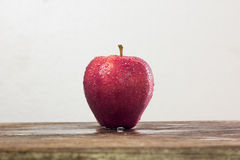 red apple with drop of water on skin put on wood table with whit Royalty Free Stock Photography