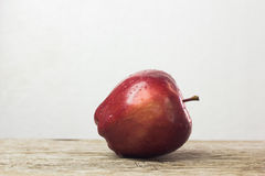 red apple with drop of water on skin put on wood table with whit Stock Photos