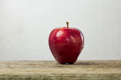 red apple with drop of water on skin put on wood table with whit Stock Photography