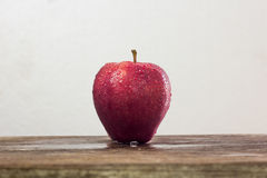 red apple with drop of water on skin put on wood table with whit Stock Image