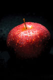 Red apple with drops on dark background Stock Photo